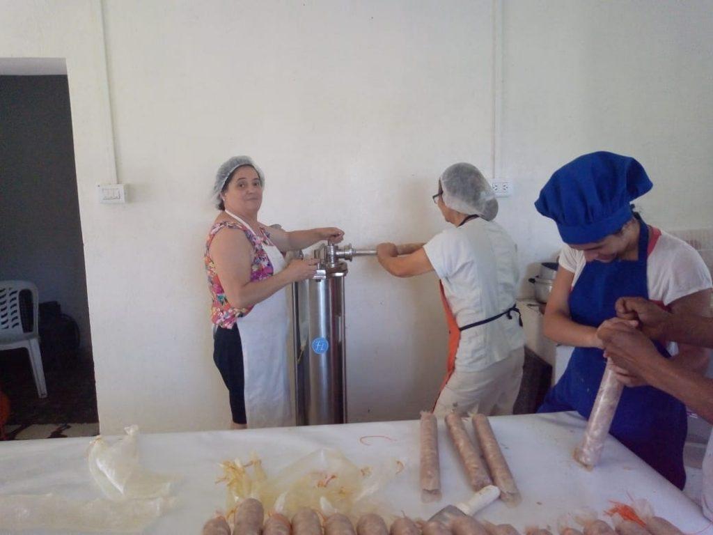 Las mujeres trabajan en la embutidora neumática, una de las máquinas que pudieron comprar a través del proyecto. Así llenan los salames. A la derecha, Carla los ata.